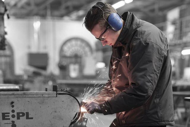 Luca werkt aan de schuurband in het staalatelier van Exclusive Steel in Made.