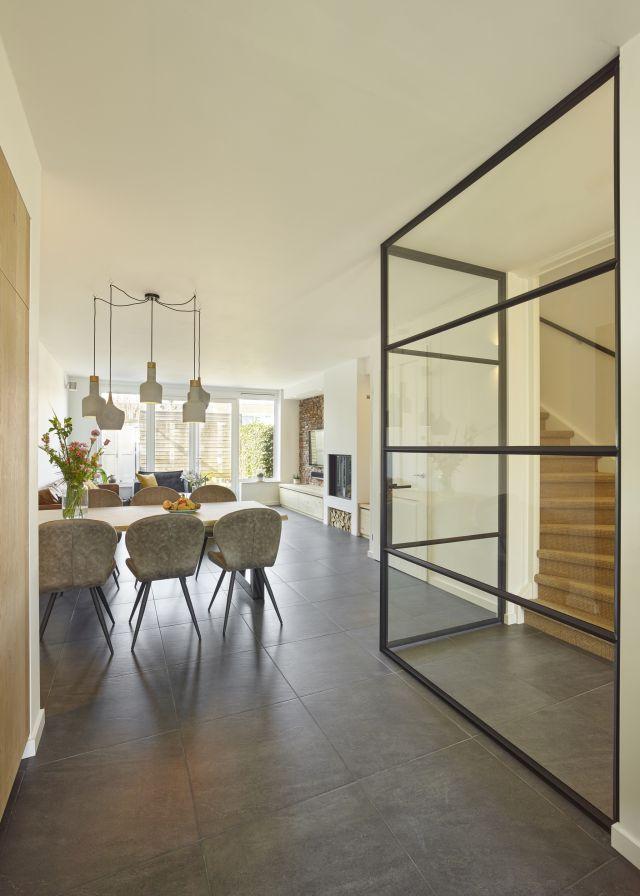 Hoekwand van glas en staal tussen hal en woonkamer zorgen voor een optimale daglichtinval.