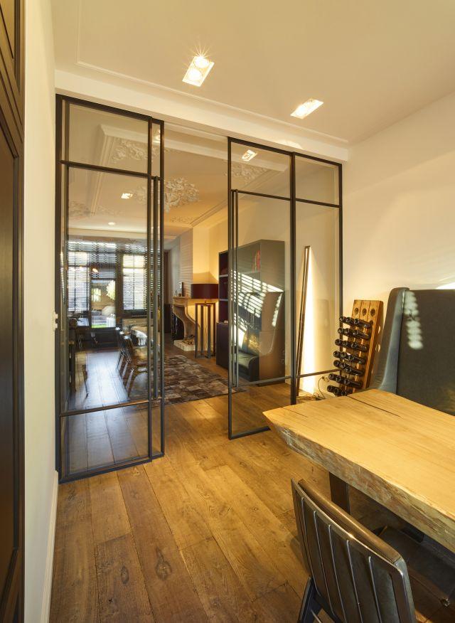 Schuifdeuren van staal met staafgreep en een vakverdeling die de hoogte van de kamer laat uitkomen.
