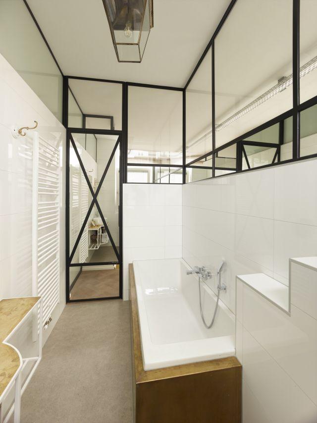 Badkamer afgescheiden door stalen pui met spiegels voor de privacy.