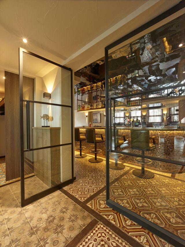 Stalen taatsdeuren met drie-vaksverdeling en staafgreep in restaurant Opporto in Scheveningen.