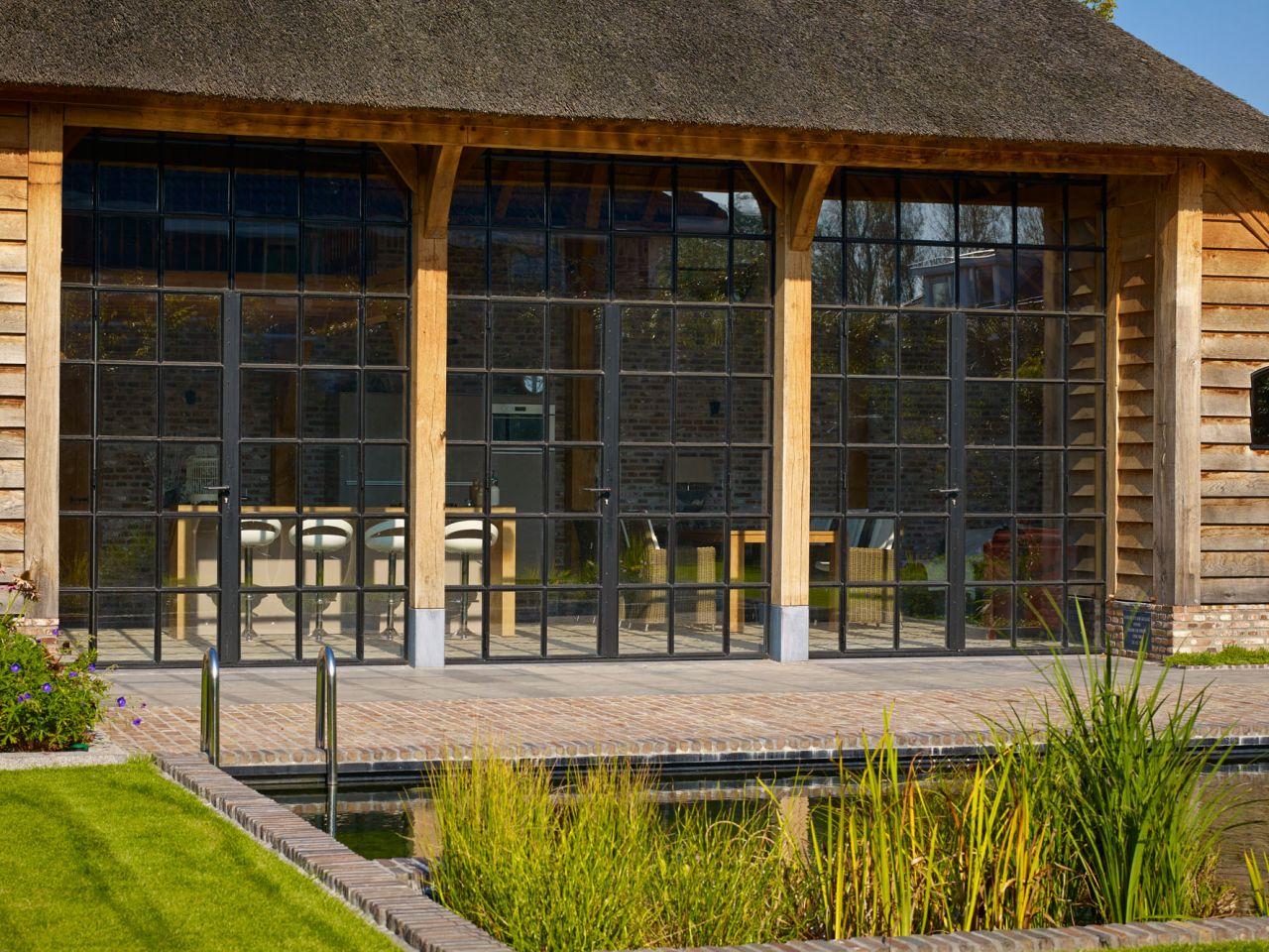 Stalen deuren met glas zorgen voor een transparante afsluiting van het bijgebouw in Werkhoven.