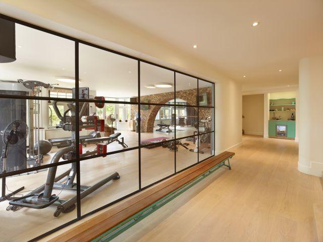 Stalen pui met drie-vaksverdeling en akoestisch glas zorgen voor een scheiding van de gym met de hal met optimale daglichtintreding.