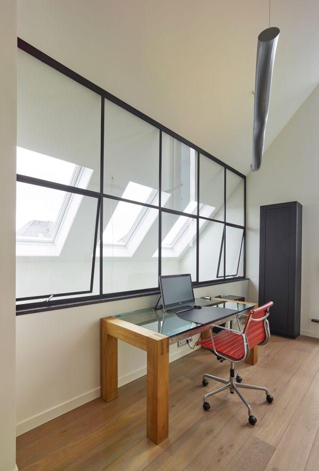 Stalen raamkozijn met openslaande kiepramen in werkkamer in Prinsenbeek.