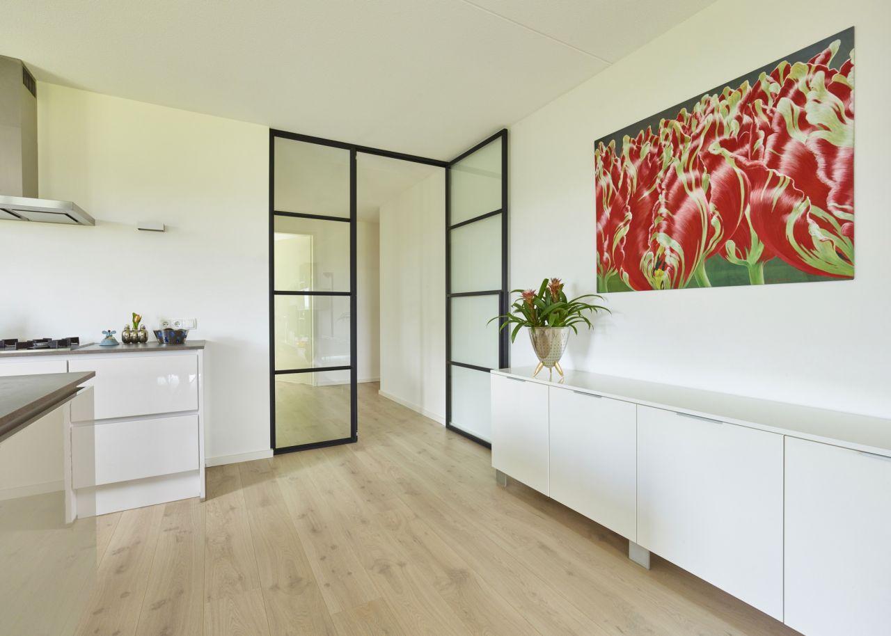 Stalen deur met zijpaneel in appartement in Teteringen.