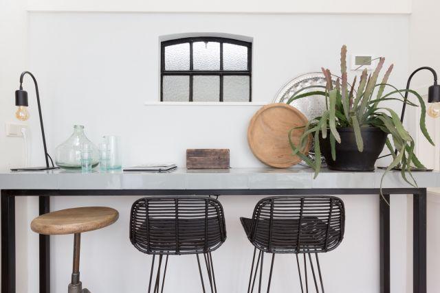 Stalen hoekpui als toegang naar trapgat voorkomt warmteverlies in de living.