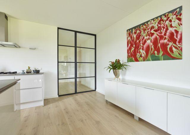 Stalen deur met zijlicht in appartement in Teteringen.