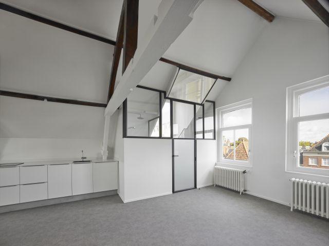 De doucheruimte in dit appartement in Dordrecht is gemaakt met een stalen pui en een stalen deur.
