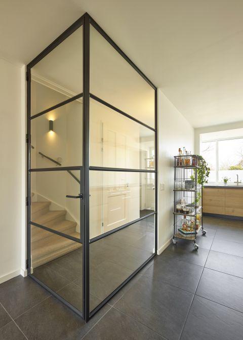 Transparante scheiding tussen woonkamer en hal door hoekwand van staal en glas. Project in Voorhout.