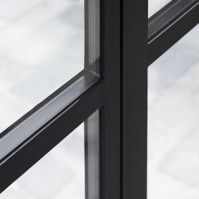 Detailfoto van de stalen buitendeuren in Made. Dubbel glas met zwarte spouw passen naadloos in de zwartstalen buitengevel.