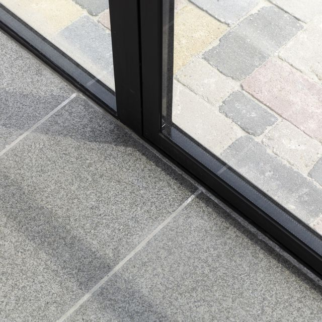 Dubbel glas met zwarte spouw in geïsoleerd profiel. Detailfoto van stalen buitendeuren in Made.