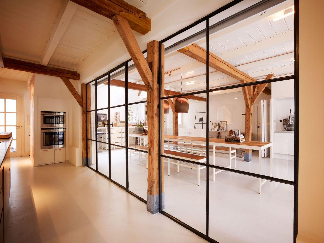 Stalen binnenkozijn als roomdivider tussen keuken en home-office in Voorburg.