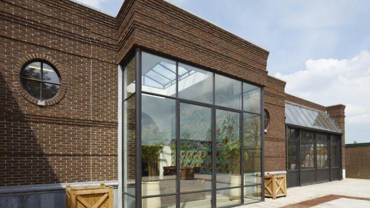 Stalen buitenpui met dubbele openslaande stalen buitendeuren. Staalprofiel met koudebrugondering. Project in Made.