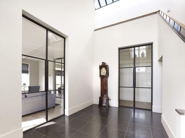 Stalen deuren in de hal zorgen voor een optimale lichtinval in Woudrichem.