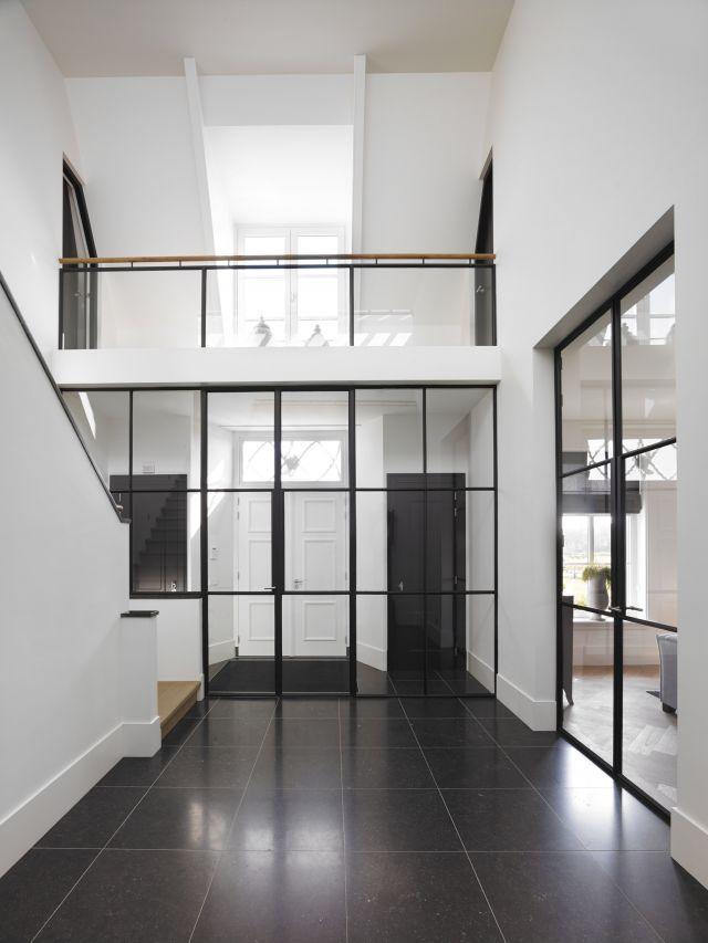 Stalen wand in van entree naar hal benadrukt de hoogte, de balustrade juist de breedte. Project in Woudrichem.