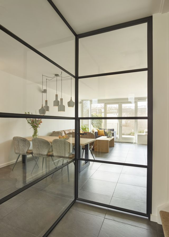 Stalen deur in hoekwand van staal en glas zorgt voor optimale lichtinval in de hal.