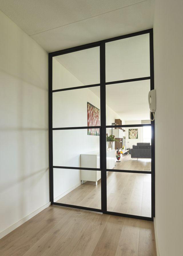 Stalen deur met glas en Paumelle scharnieren en zijpaneel in appartement in Teteringen.