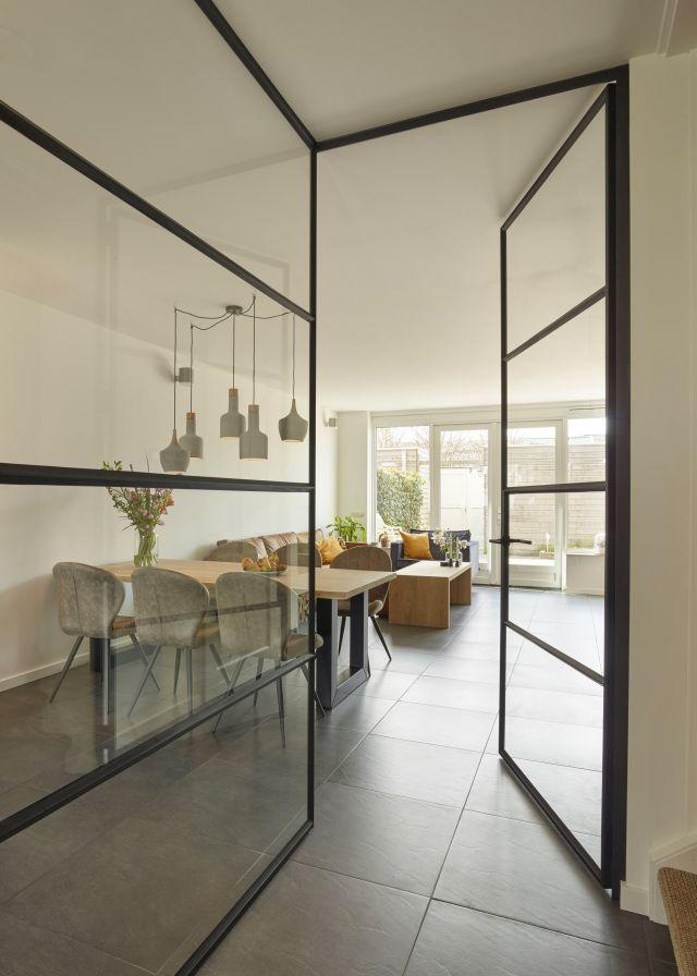 Stalen hoekwand met loopdeur en viervaksglasverdeling zorgt voor een afgesloten maar toch transparante scheiding tussen hal en woongedeelte.