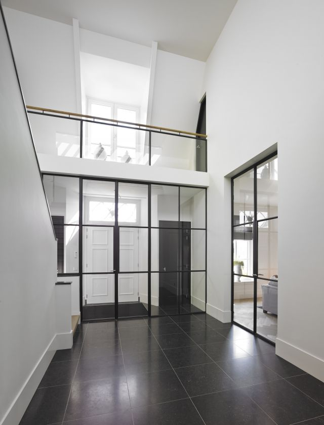 Hal met stalen pui en balustrade benadrukken zowel de hoogte als de breedte van de ruimte.