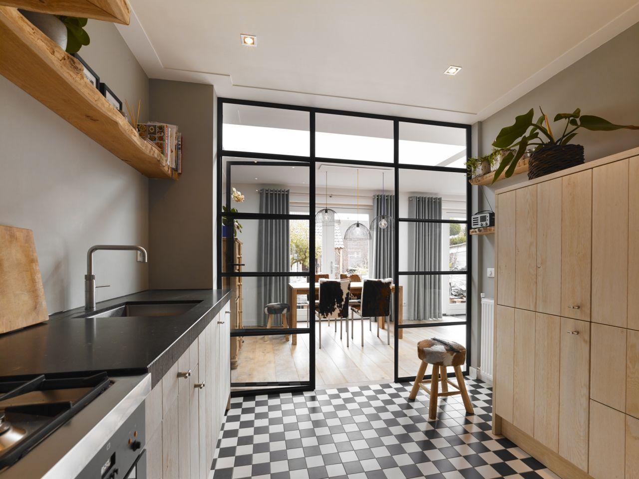 Stalen pui tussen keuken en woonkamer met twee zijlichten en één stalen deur in Oosterhout.