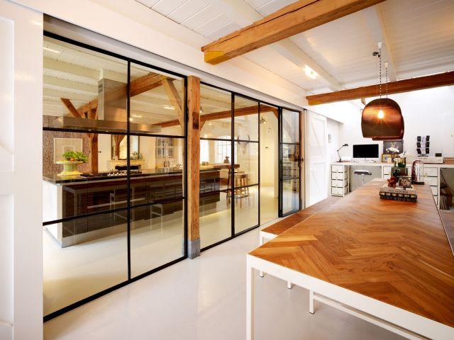 Stalen wand openslaande deuren zorgen voor een transparante afscheiding van het leef- en werkgedeelte.