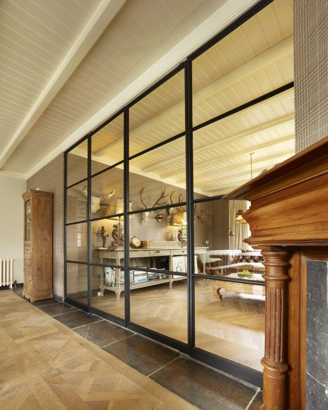 Stalen taatsdeuren met slank taatsscharnier in de onderbalk verwerkt. Project in Made.