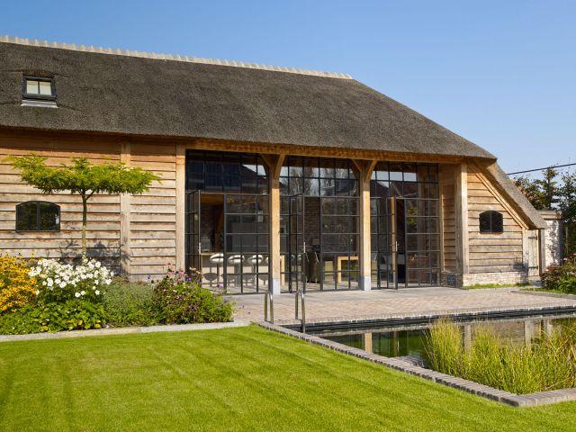 Stalen deuren in landelijke vakverdeling in een eikenhouten bijgebouw met rieten dak in Werkhoven.