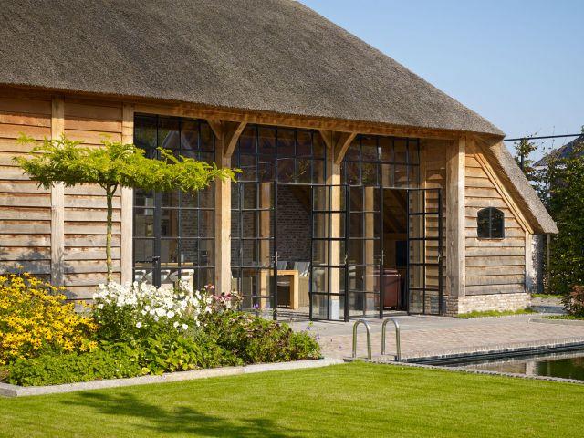 Openslaande stalen deuren in een bijgebouw van eikenhout geven toegang tot het terras in Werkhoven.