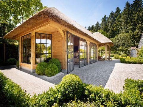Bijgebouw van eikenhout met een rieten dak een stalen ramen en kozijnen in Gent België.