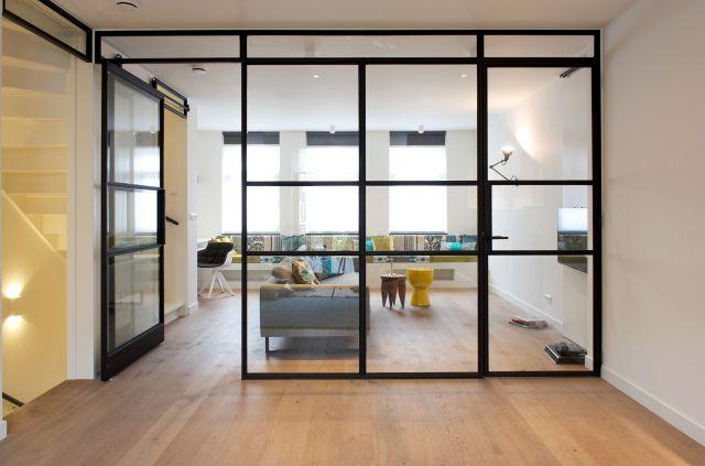 Stalen schuifwand met vakverdeling die optisch afsluit en geborgenheid en comfort biedt. Interieurarchitect Inge Bouman Haarlem.