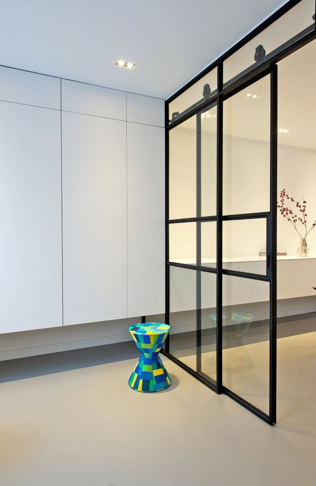 Stalen schuifdeuren met wielen in het zicht. Project in samenwerking met interieurarchitect Inge Bouman Haarlem.