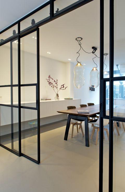 Stalen schuifdeuren met glas. Het bovenlicht zorgt ervoor dat de stalen wielen aan beide zijden zichtbaar zijn. Interieurarchitect Inge Bouman Haarlem.
