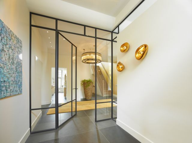 Stalen wand met open deur naar trappenhuis in Amsterdam.